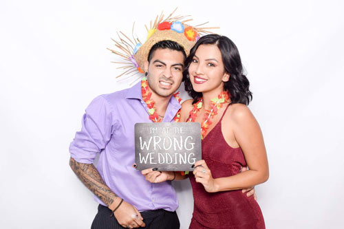 A couple holding a sign saying I'm at the wrong wedding